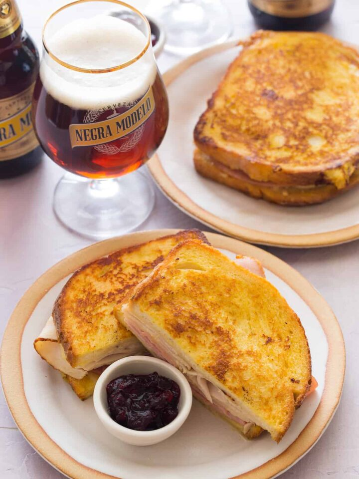 Monte cristo sandwiches with a ramekin of cranberry jam on plates with beer.