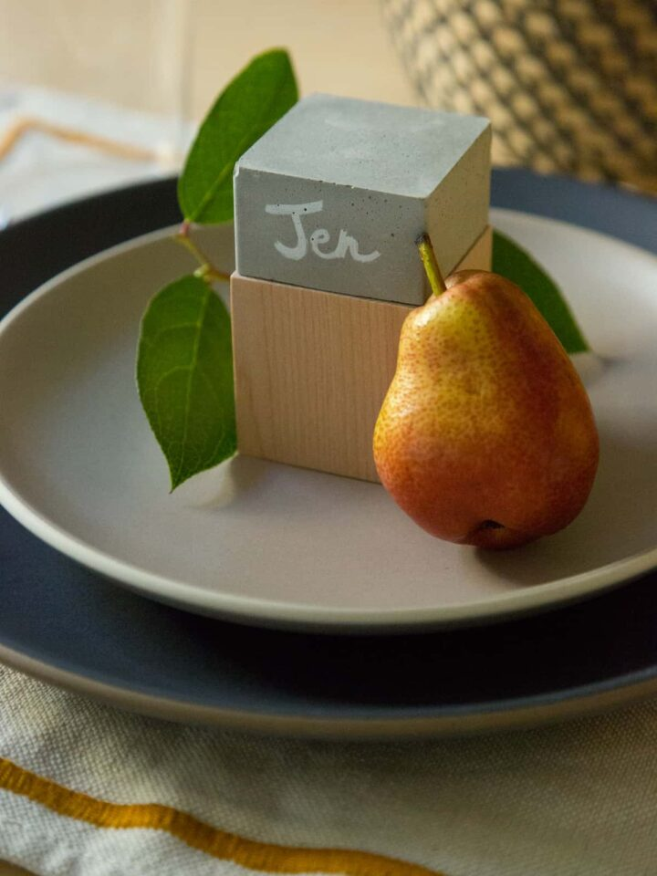 A DIY cement and wood place card with a pear on a place setting.