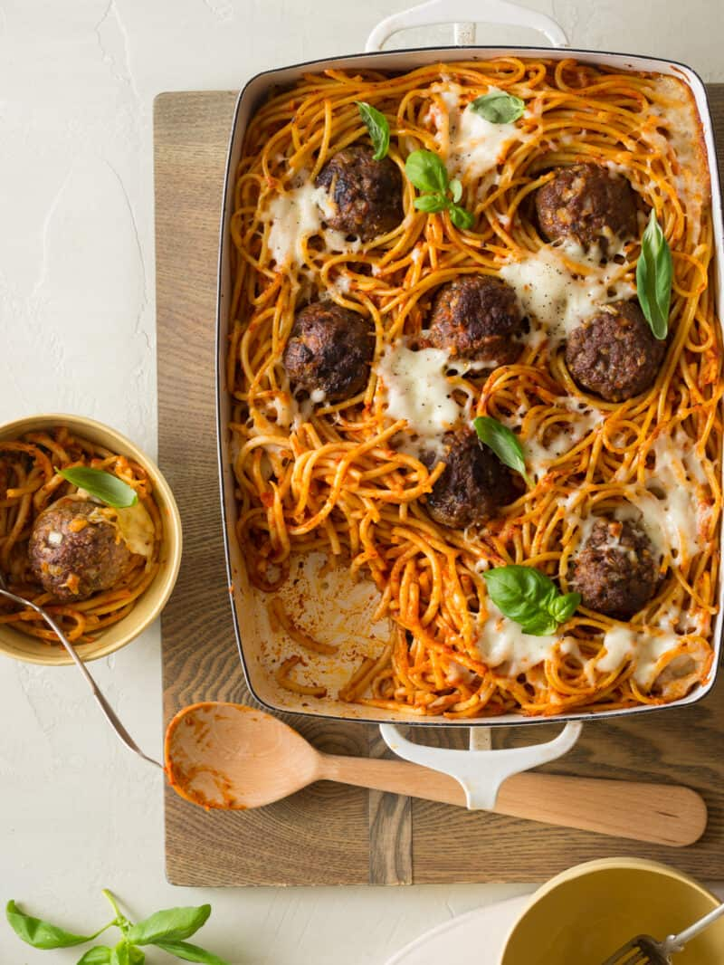 Baked meatballs over bucatini in a pan with a bowl served and a wooden spoon.