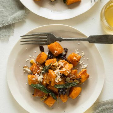 Plates of sweet potato gnocchi with fried sage dried cherries and toasted hazelnuts with a fork.