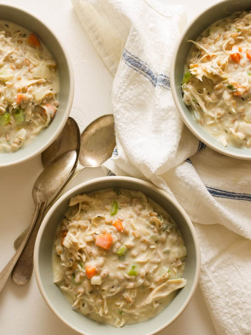 Creamy chicken and faro soup in bowls with linens and spoons.