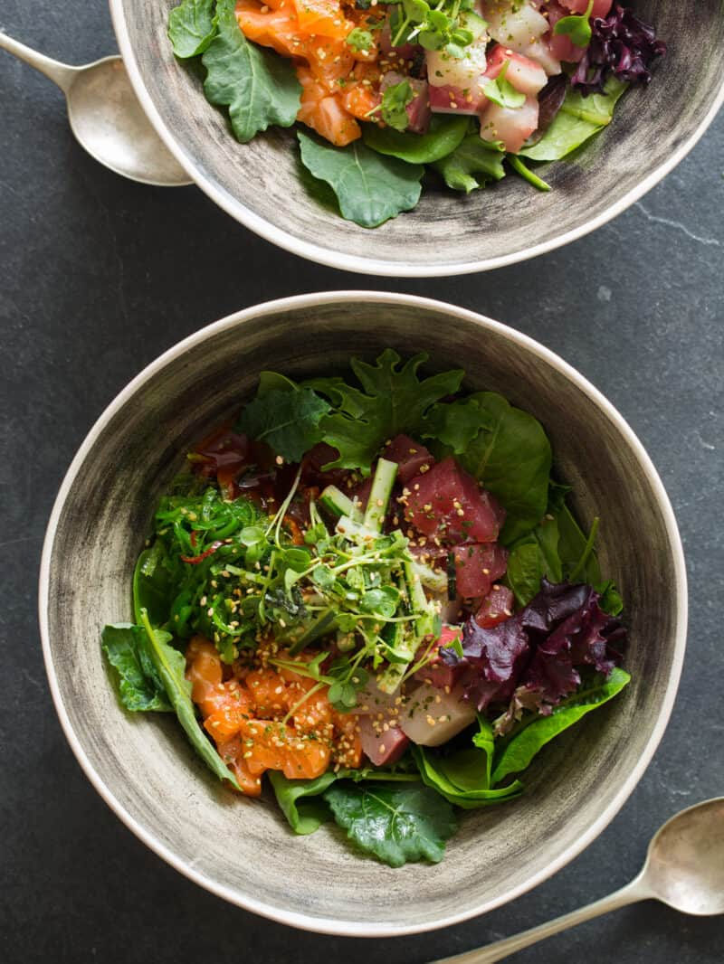 Korean spicy sashimi salad in gray bowls.