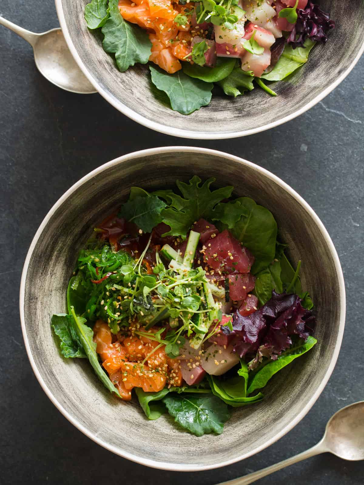 Korean spicy sashimi salad in gray bowls.