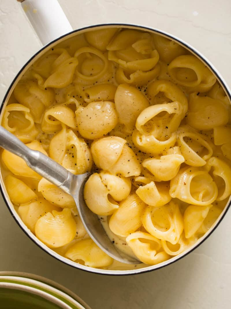 A bowl of creamy stovetop mac and cheese with a spoon.
