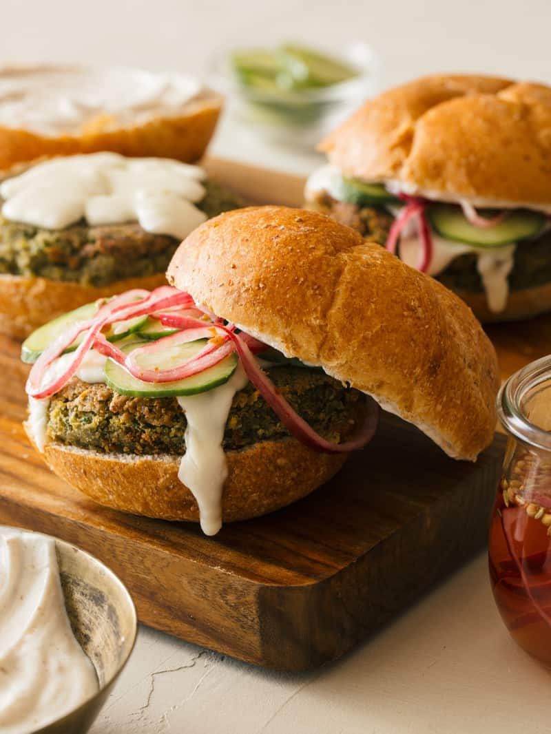 A close up of falafel burgers with roasted garlic aioli, quick pickled red onions, and cucumbers.