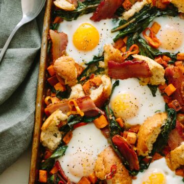 A close up of a savory breakfast pan with linens and a spoon.
