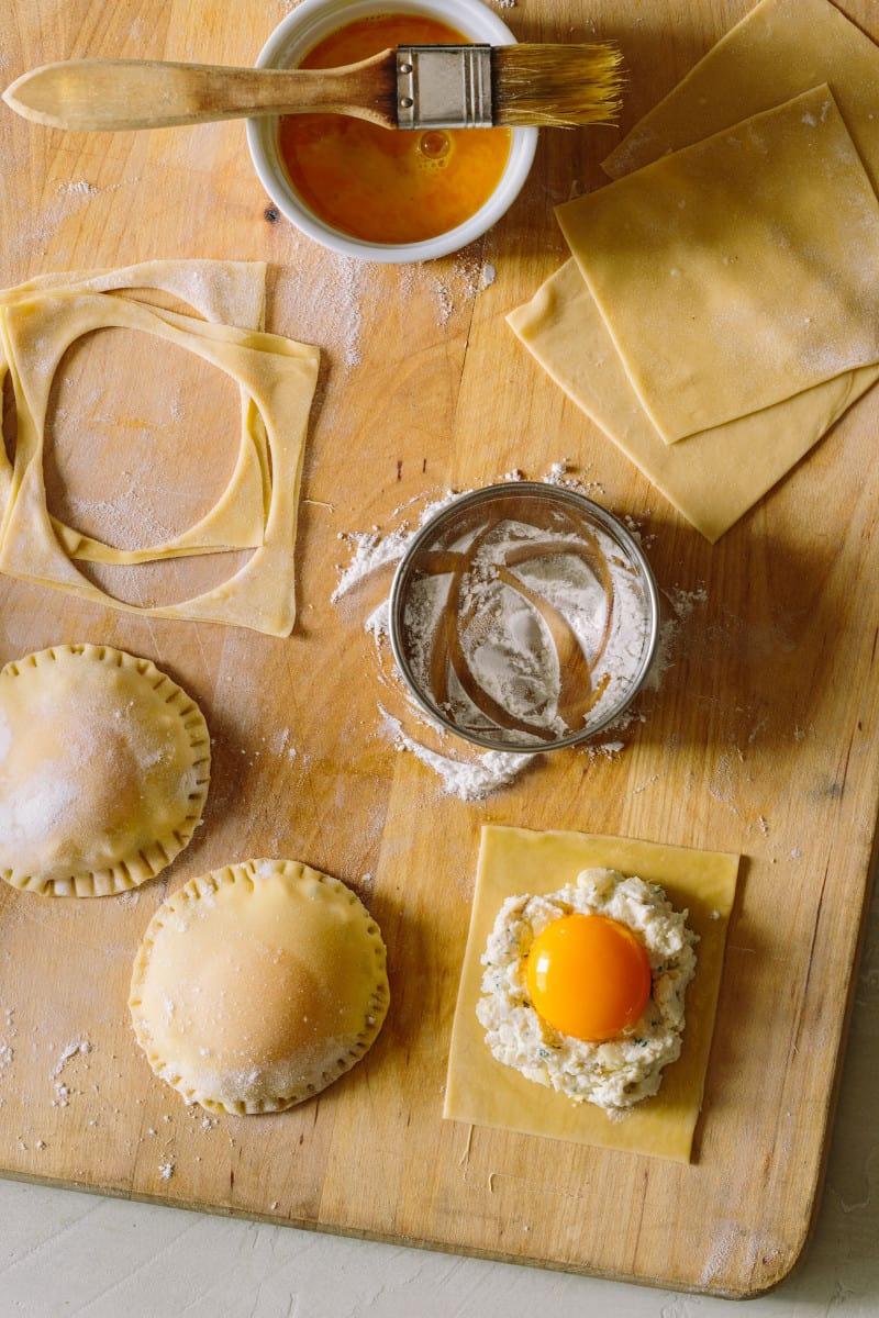 Process to make chicken and tarragon poached yolk stuffed ravioli on a cutting board.