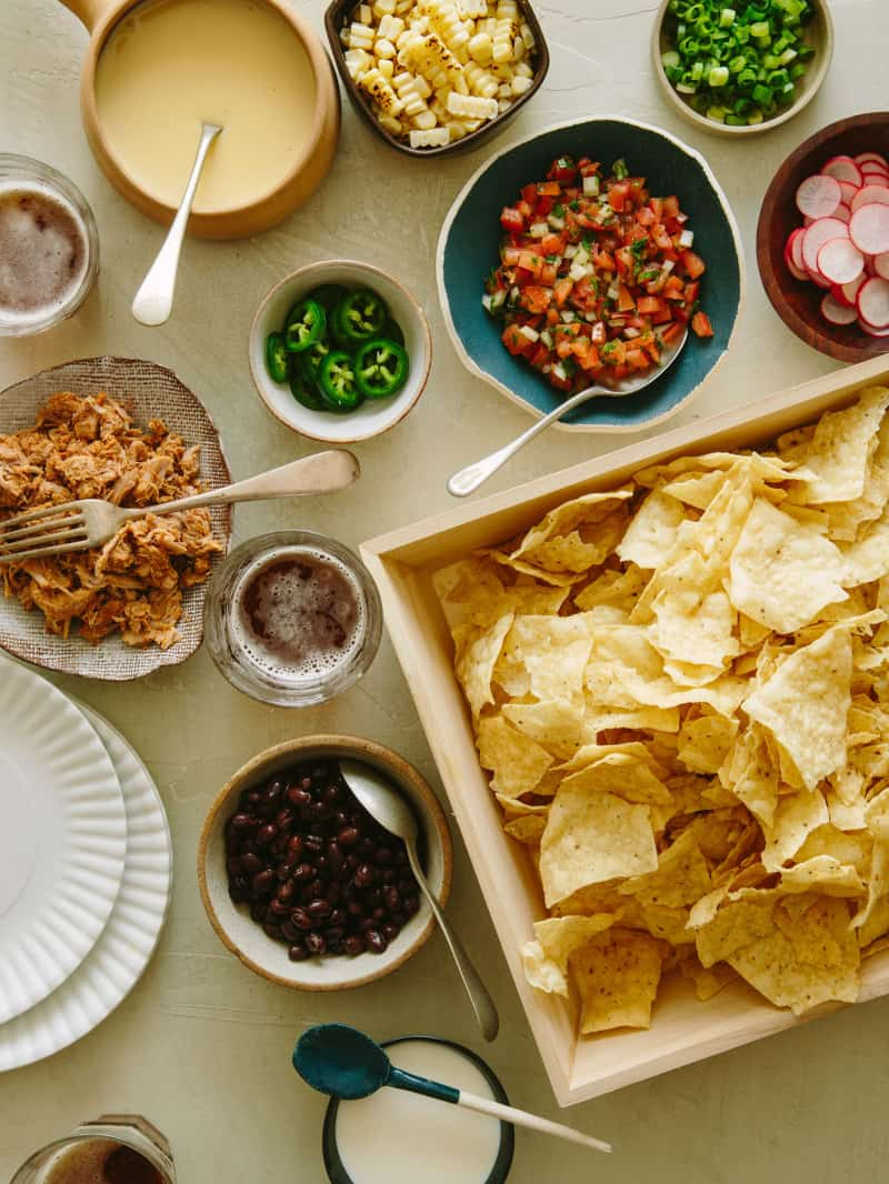 Chips in a tray and toppings in different bowls for DIY nacho bar for Super Bowl.