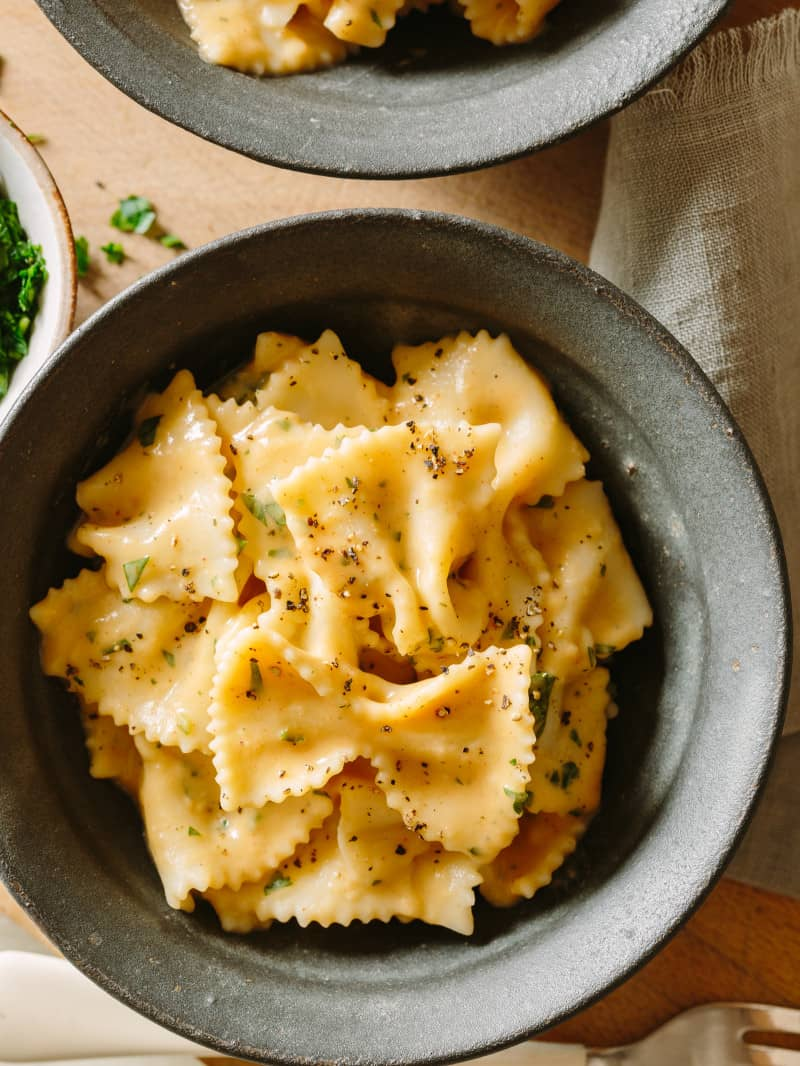 A close up of farfalle with creamy white bean and roasted garlic sauce in a bowl.