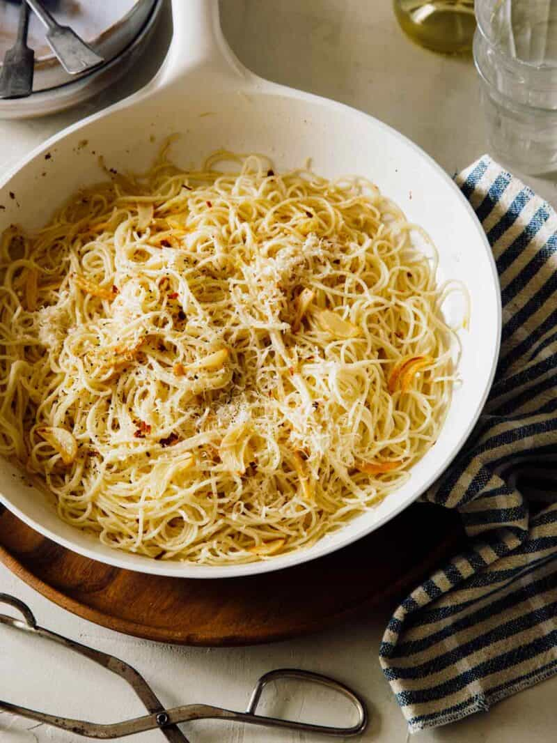 Capellini pasta in a skillet with parmesan on top.