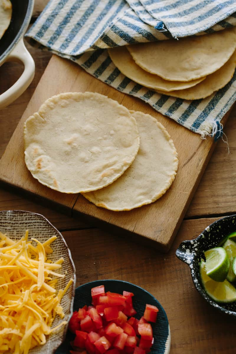 Homemade corn tortillas on a cutting board with toppings next to it.