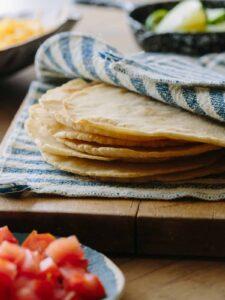 Homemade corn tortillas a hand towel on a wooden cutting board.