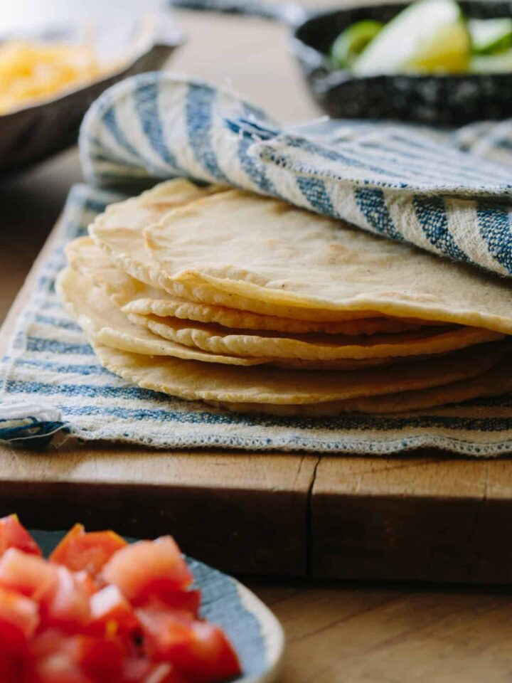 Homemade corn tortillas a hand towel on a wooden cutting board.