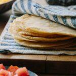 DIY hard and puffy corn tortillas, flat and folded on a cutting board.