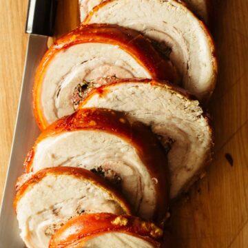 A close up of sliced pork belly porchetta with a knife.