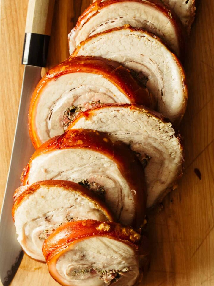 A close up of sliced pork belly porchetta with a knife.  A delicious Easter Dinner recipe.
