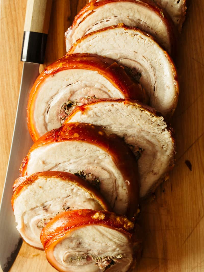 A close up of sliced pork belly porchetta with a knife.