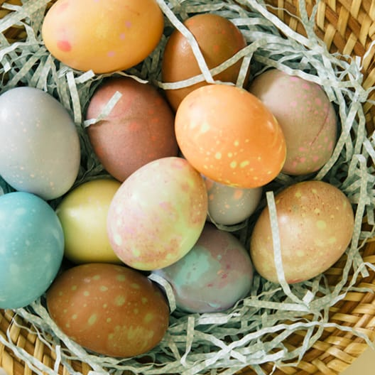 Spotted dyed easter eggs in a basket.