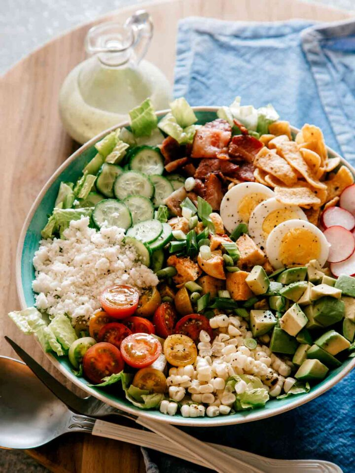A plate of southwestern style cobb salad with cilantro ranch dressing on the side.