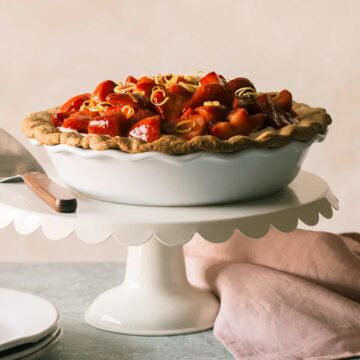 A whole strawberry cream pie on a white cake stand with a pie server.