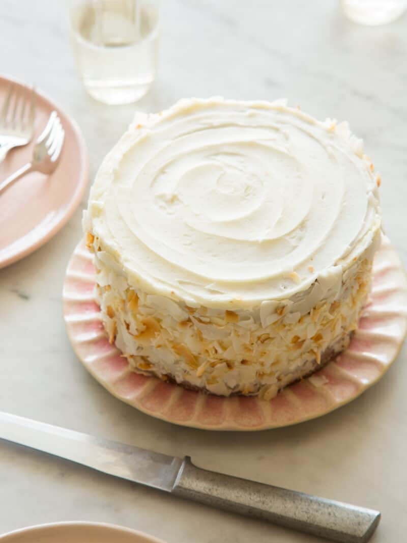 A whole coconut cake next to plates with forks.