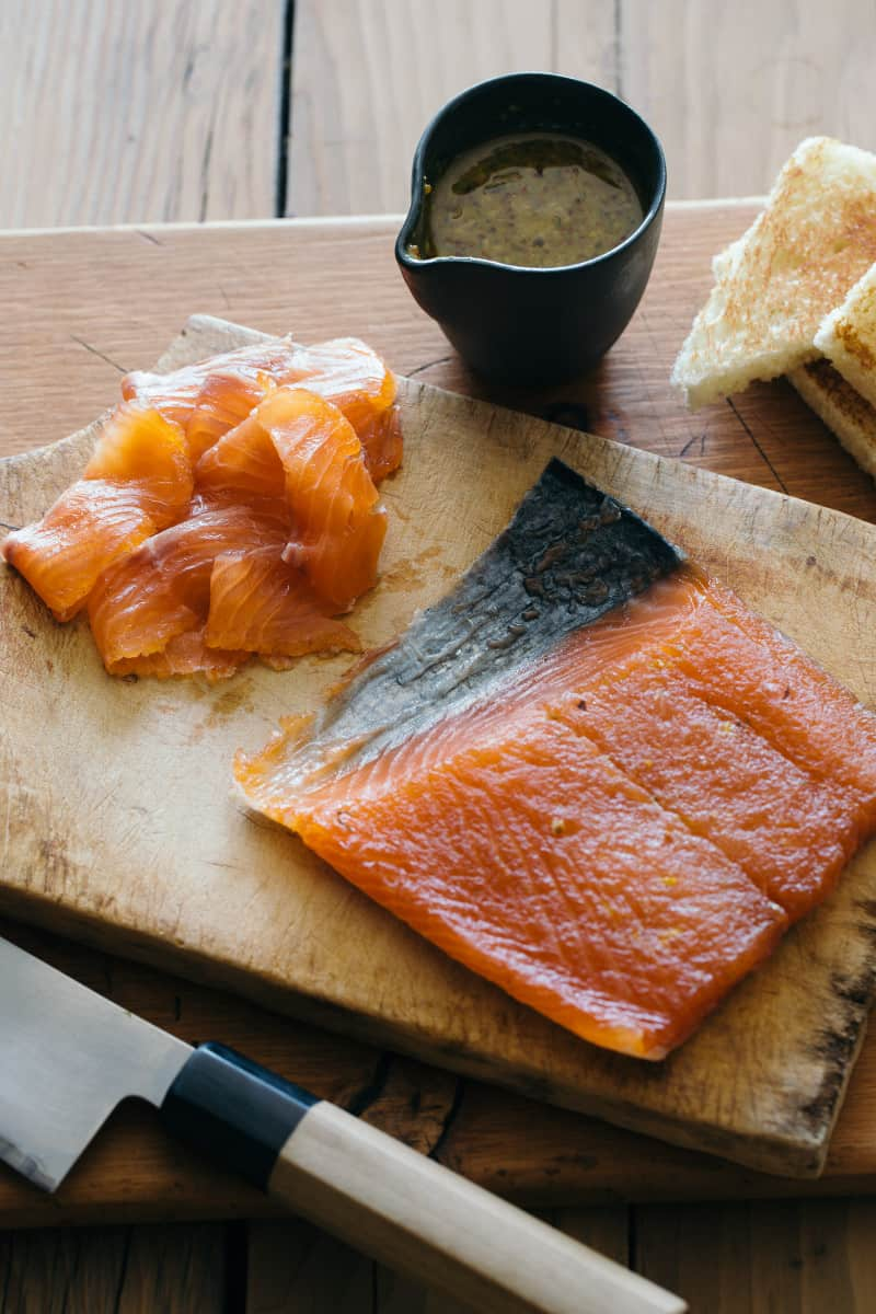 A piece of salmon with slices on a wooden cutting board and sauce on the side.