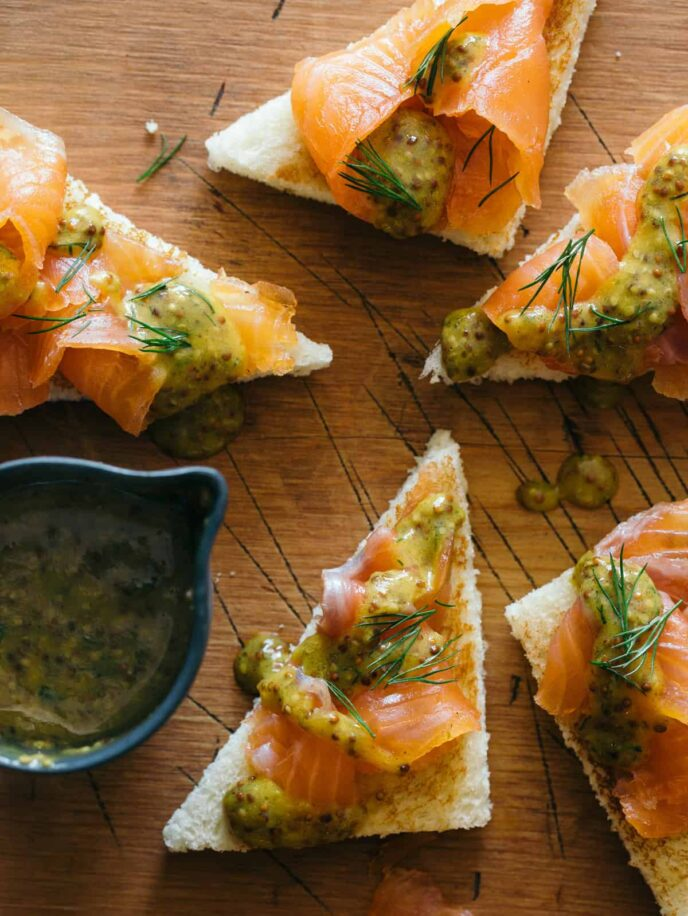 Slices of DIY gravlax with whole grain mustard sauce drizzled and on the side.