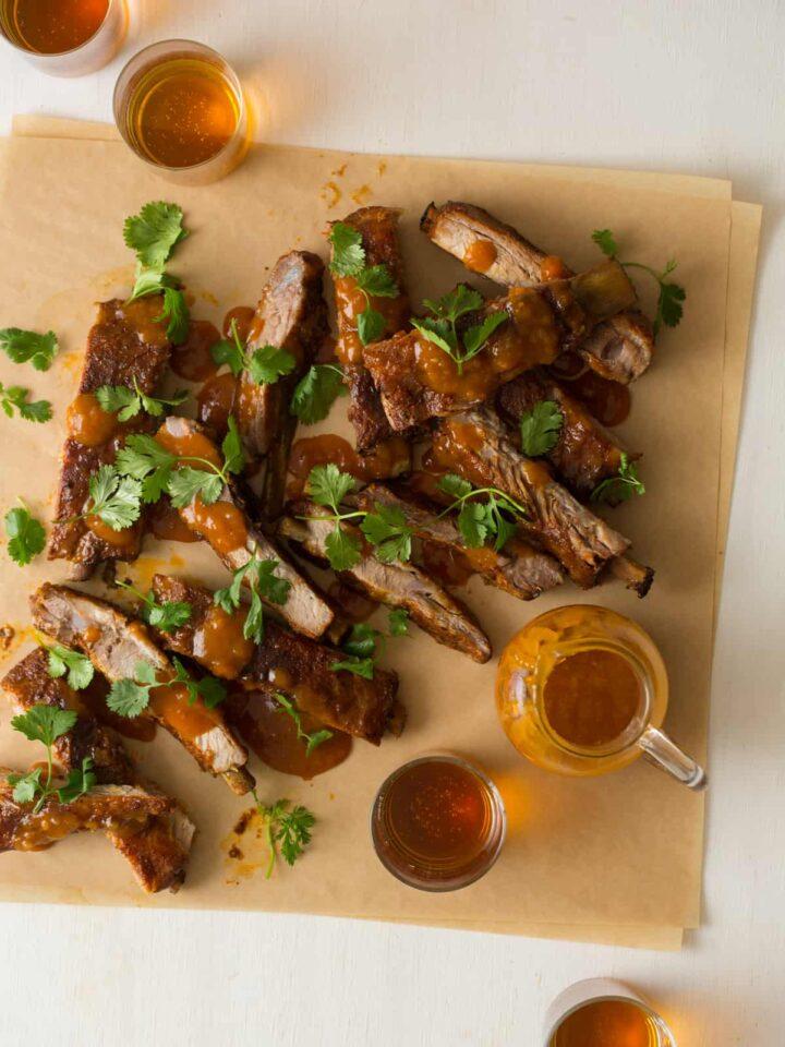 Mango habanero glazed spare ribs garnished with cilantro and extra glaze on the side.