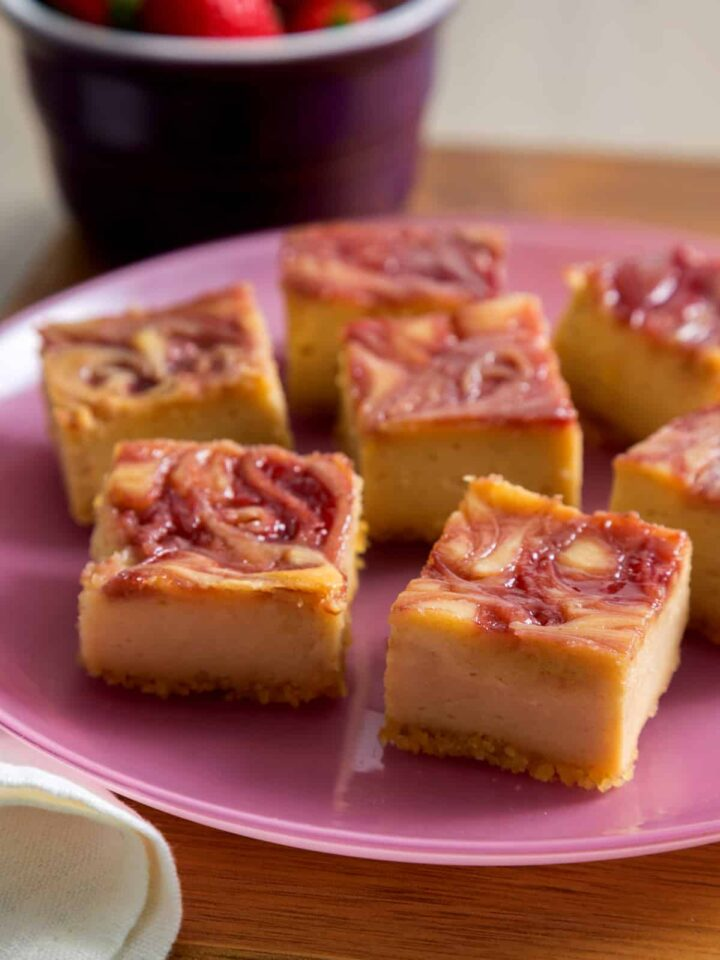 A plate of peanut butter and jelly cheesecake bars with potato chip crust.