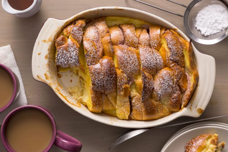 Stacked and stuffed baked French toast with a piece taken out next to coffee.