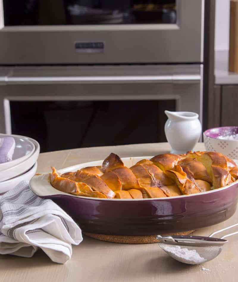 Stacked and stuffed baked French toast in front of an oven, next to plates and linens.