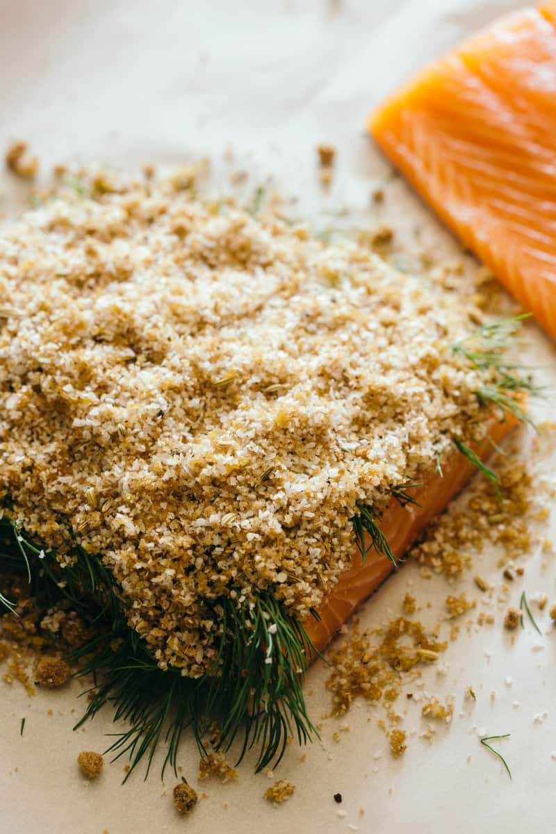 A close up of salmon with cure mixture and dill on top.