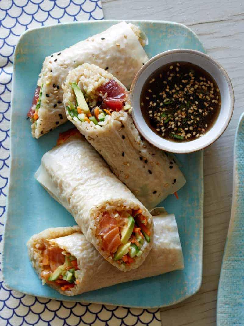 Poke burritos cut in half on a platter with a ramekin of dipping sauce.