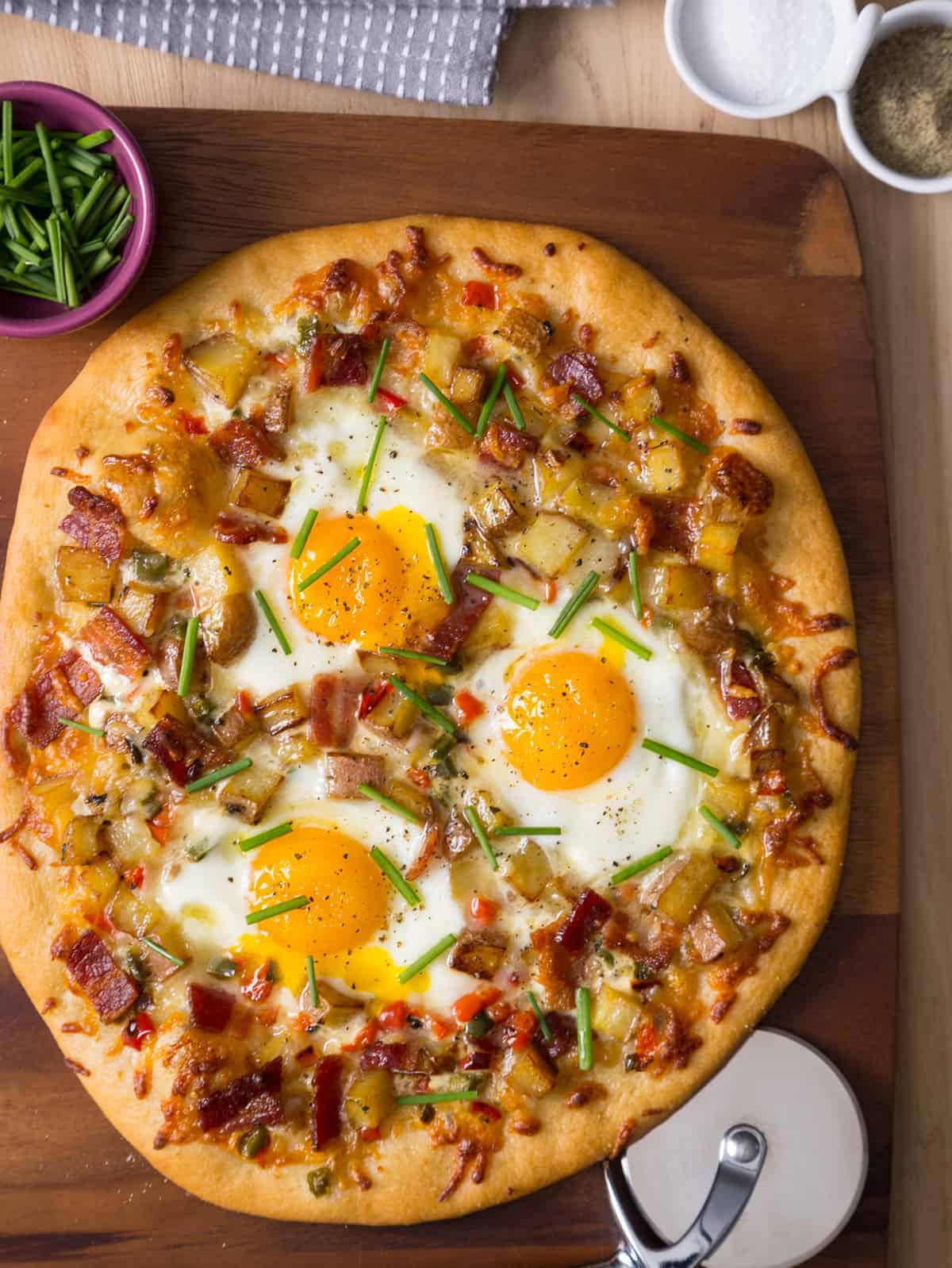 A breakfast pizza on a wooden cutting board with a bowl of chives on the side.