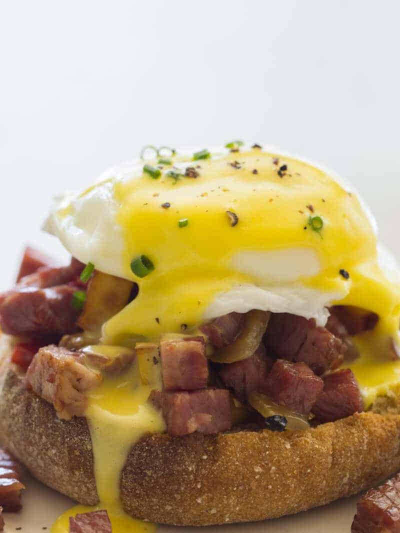 A close up of corned beef hash eggs benedict.
