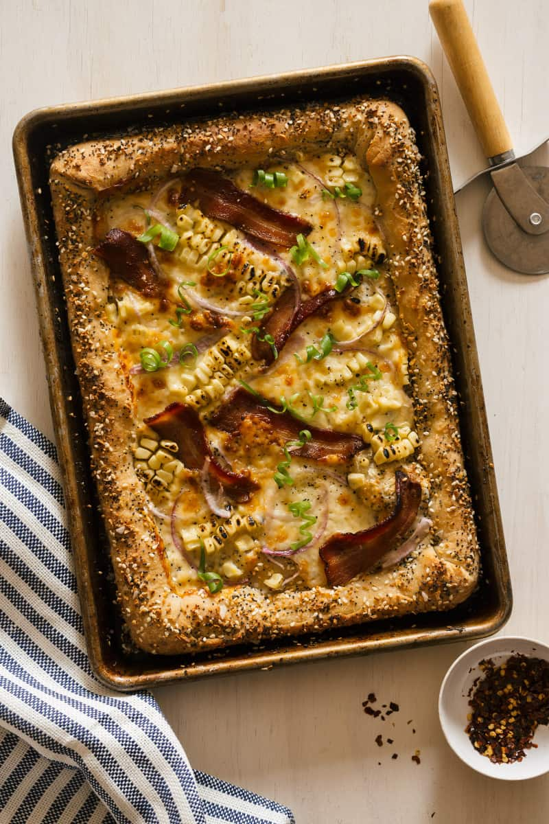 """Charred corn and bacon pizza with cream cheese stuffed """"everything"""" crust with a pizza cutter wheel."""