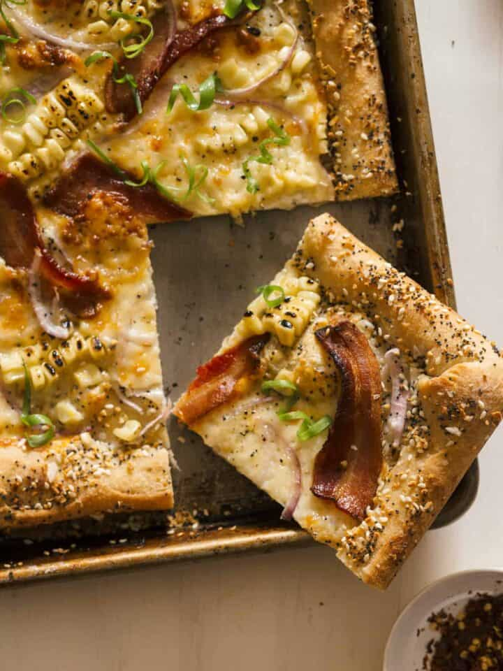 """A corner slice of charred corn and bacon pizza with cream cheese stuffed """"everything"""" crust."""