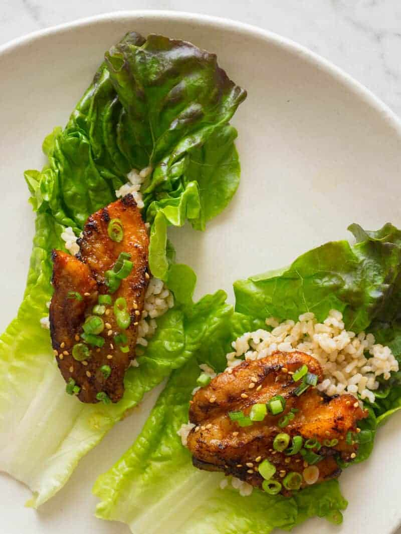 Korean style marinated spicy pork belly on brown rice and a lettuce cup.