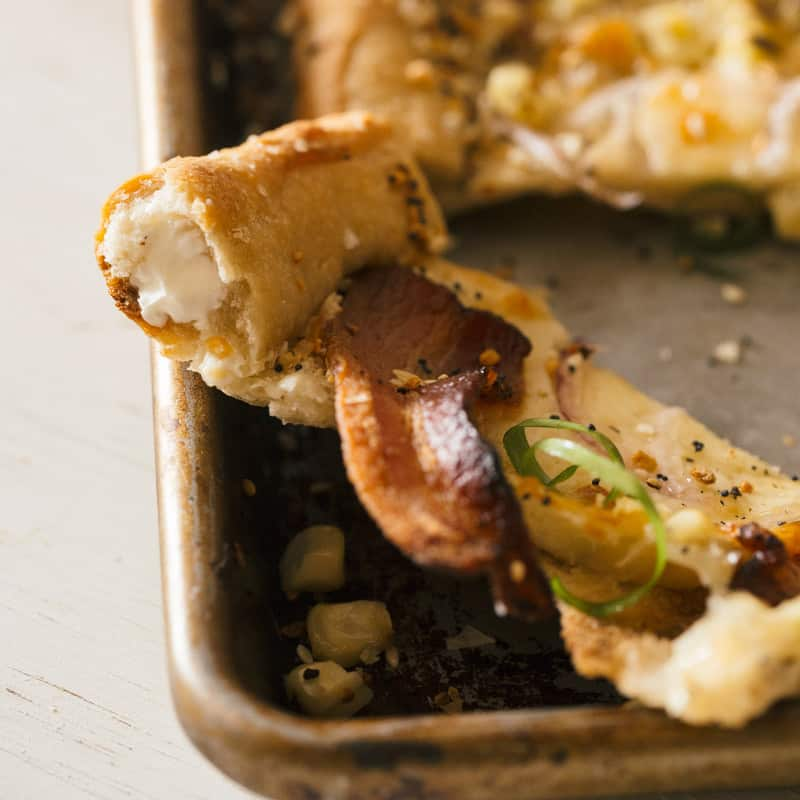 """A close up of charred corn and bacon pizza with cream cheese stuffed """"everything"""" crust."""