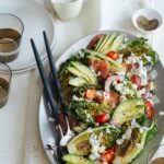 Grilled BLTA gem salad on a platter with serving utensils, plates, and drinks.