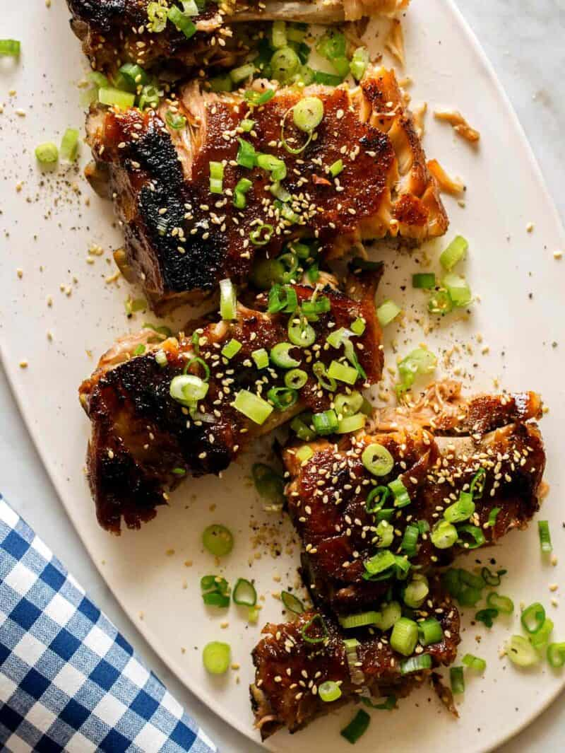 Honey Hoisin Baby Back Ribs recipe on a platter with green onions and sesame seeds.