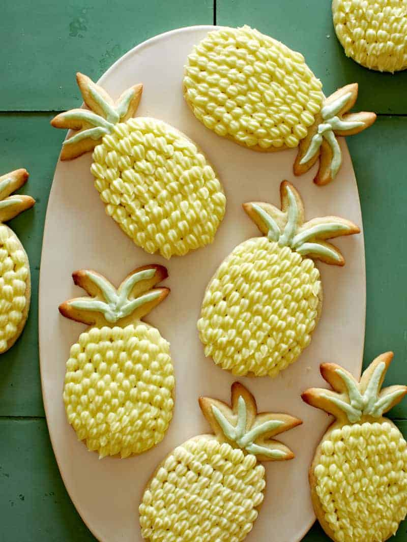 Lime sugar cookies with pineapple buttercream on a platter.