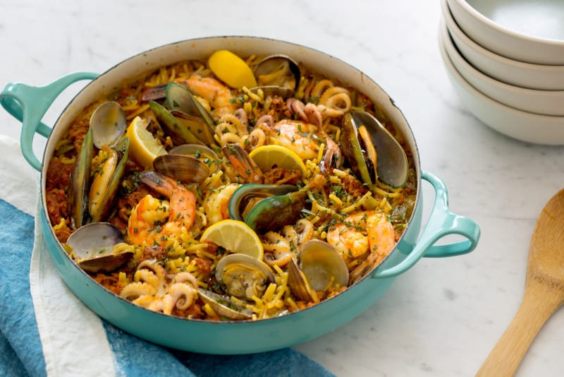 Seafood Fideua in a pot with a stack of plates next to it.