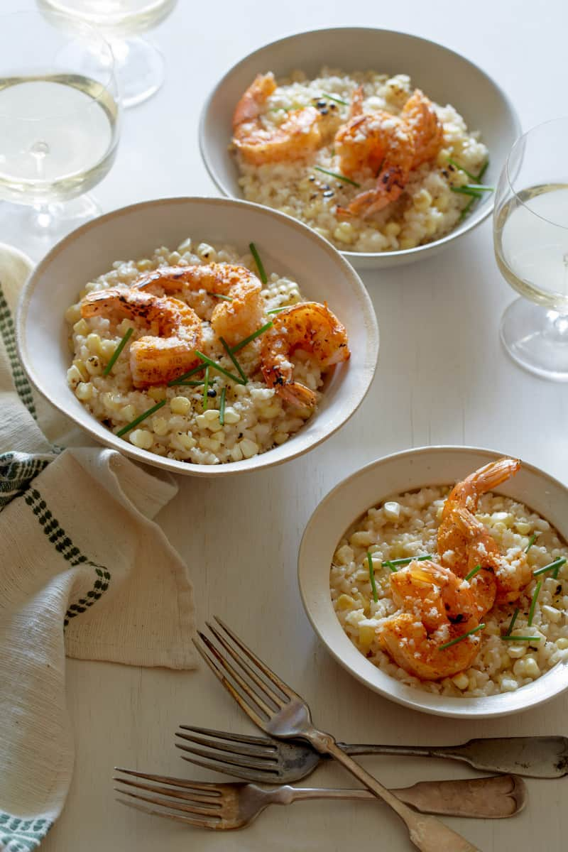 Bowls of sweet corn risotto and Cajun shrimp with forks and drinks.