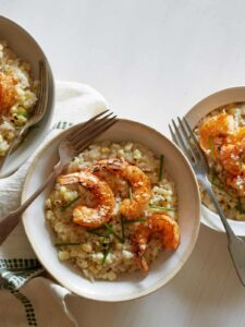 Bowls of sweet corn risotto with Cajun shrimp and forks.