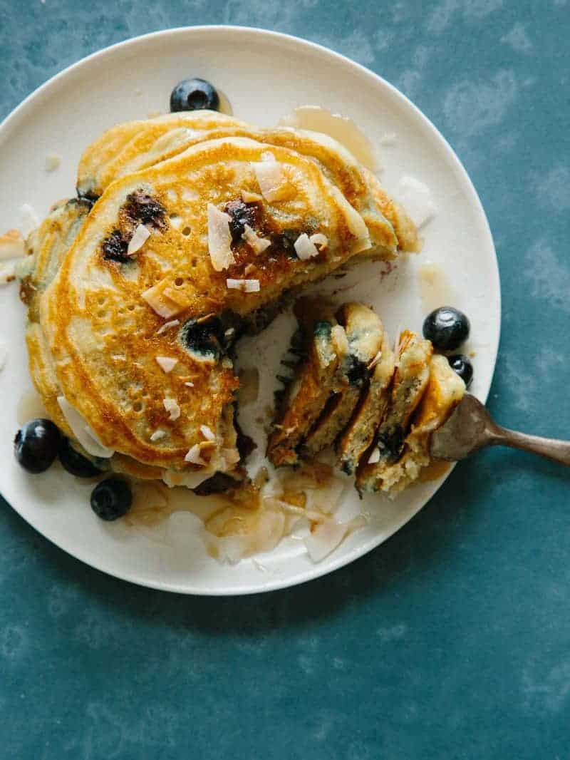 A plate of brown sugar, coconut, blueberry pancakes with a bite on a fork.