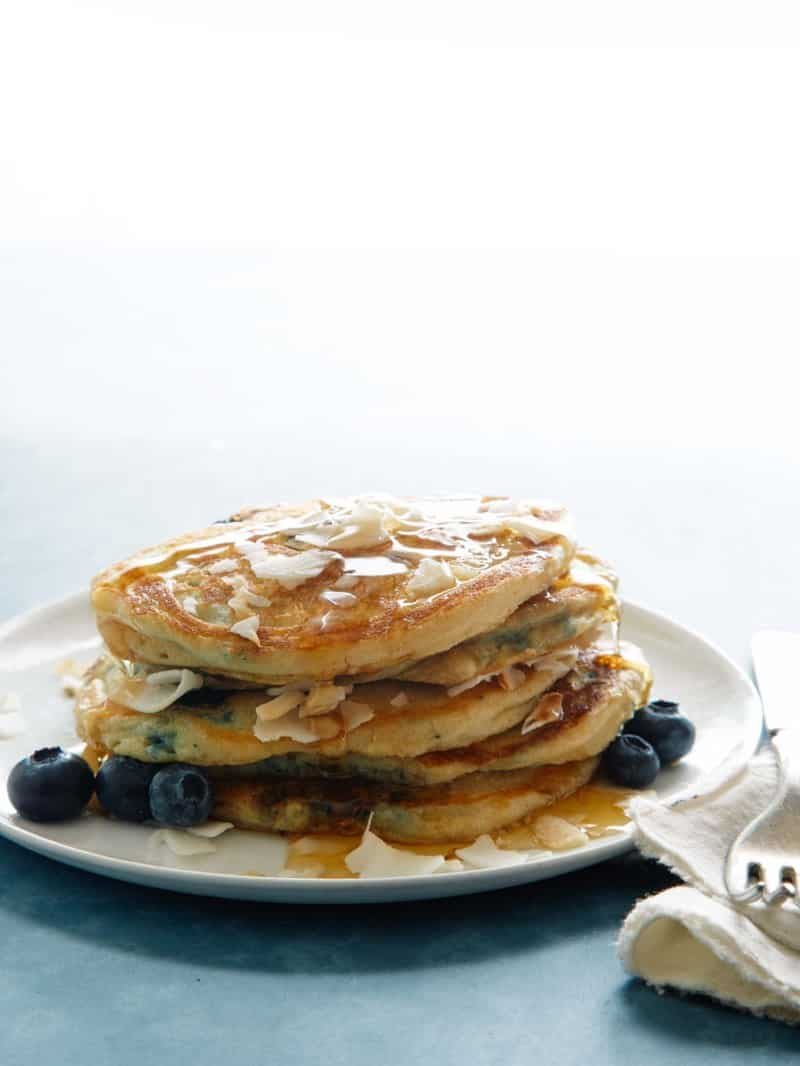 A stack of brown sugar, coconut, blueberry pancakes with a fork.