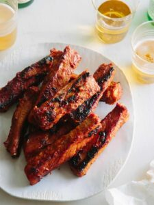 A plate of spicy marinated and grilled spare ribs next to drinks.