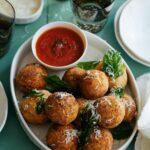 Mozzarella stuffed chicken parmesan meatballs with marinara sauce on the side.