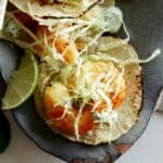 A close up of beer battered shrimp tacos with lime wedges.